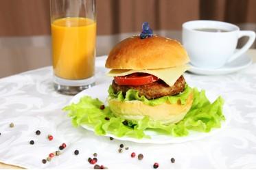 Гамбургер с с ветчиной, соусом-на основе кетчупа и майонеза, зеленью петрушки, свежим помидором и сыром